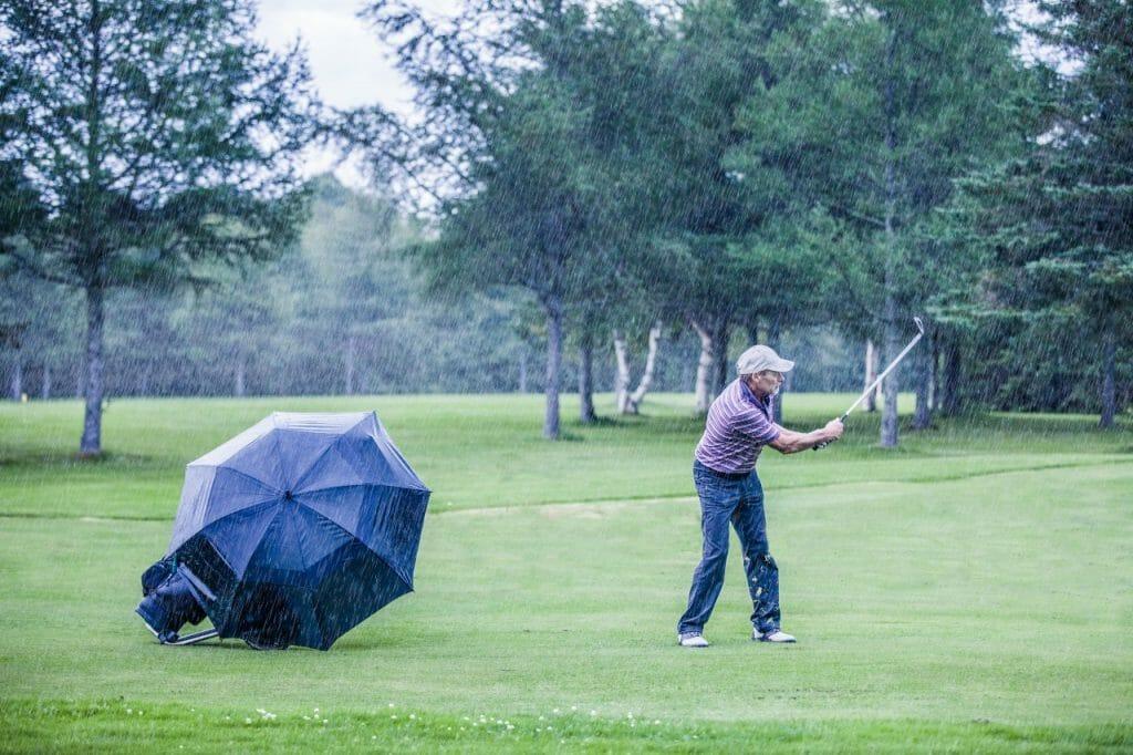 golf umbrella blowing in the rain